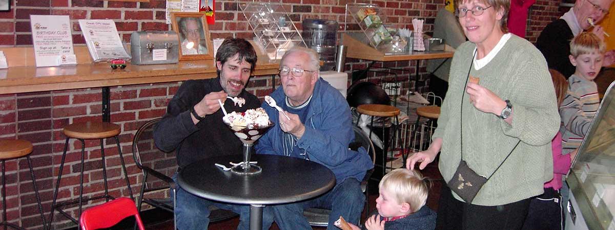 Men enjoying massive ice cream sundae (slide)
